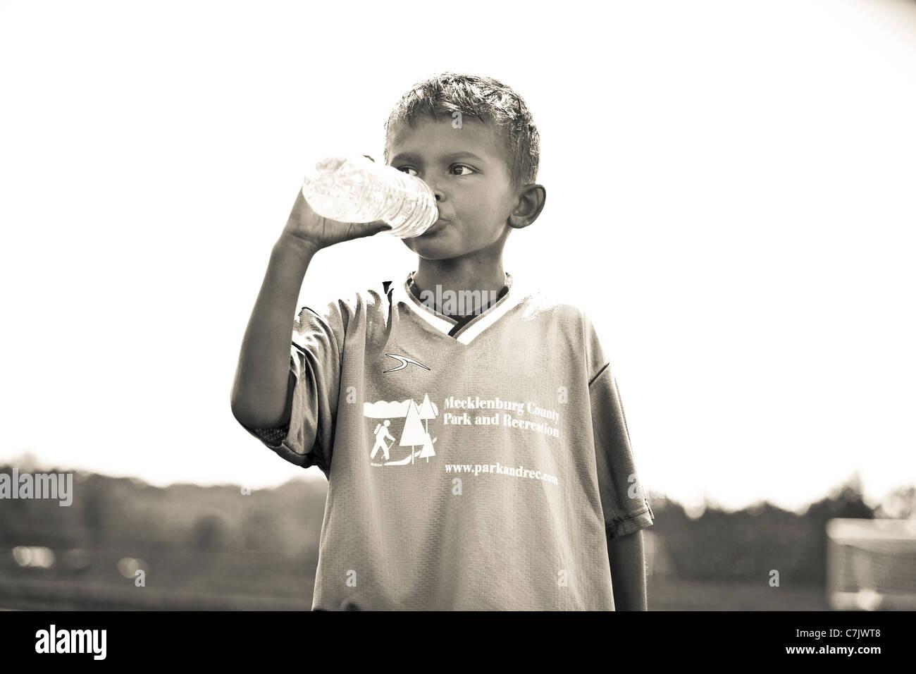 portrait of boy drinking bottled water - Stock Image