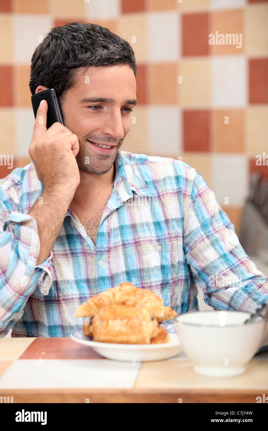 Man taking a call at breakfast - Stock Image