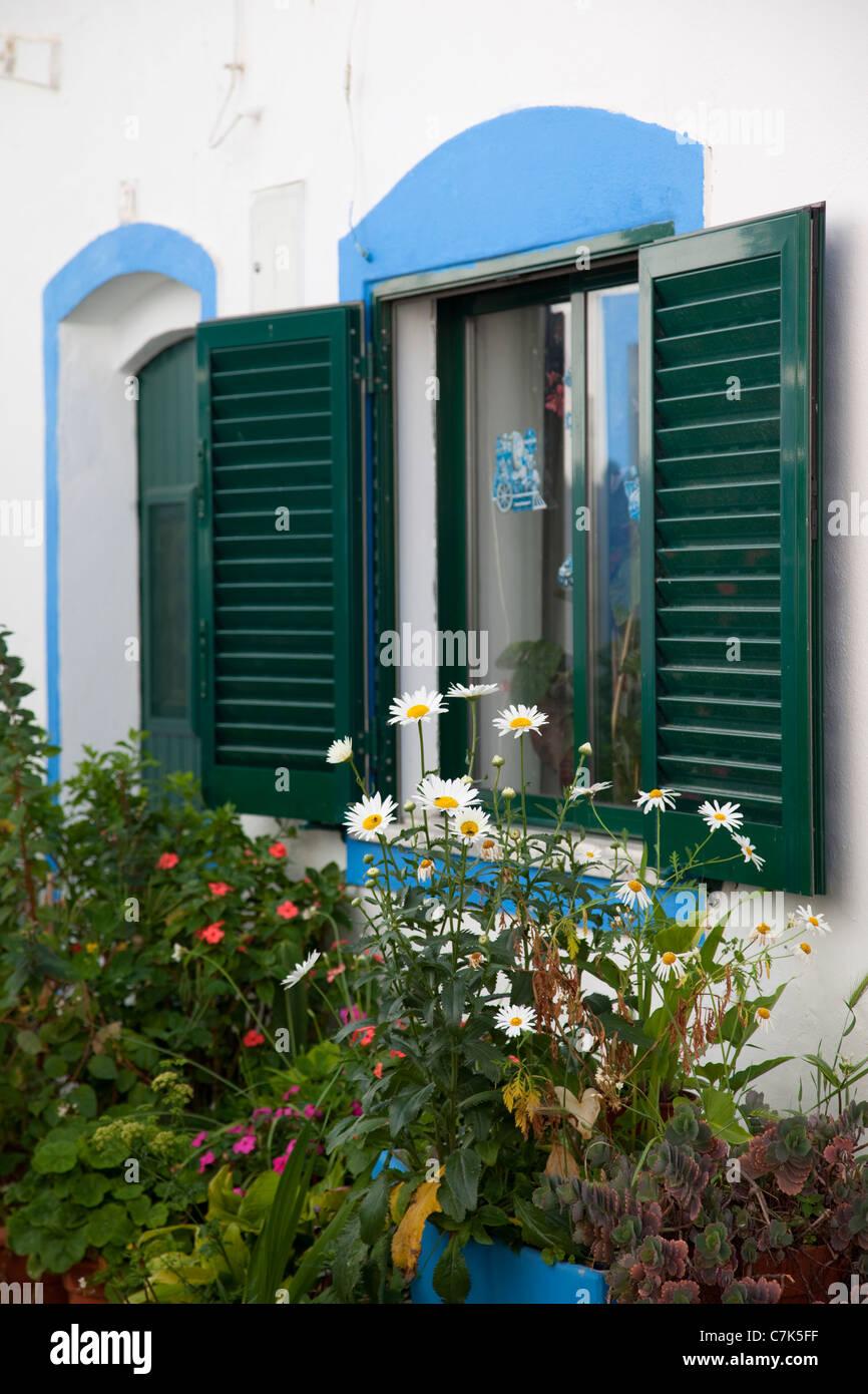 Portugal, Algarve, Ferragudo, Shuttered Windows & Flowers - Stock Image