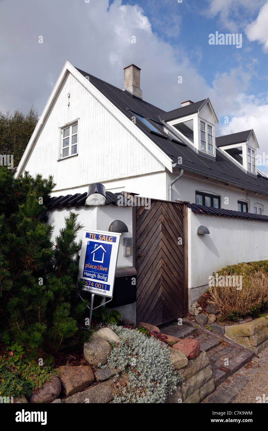 Restored, white fisherman's house for sale on the coastal road in Rungsted, Denmark. Estate agent for sale sign - Stock Image