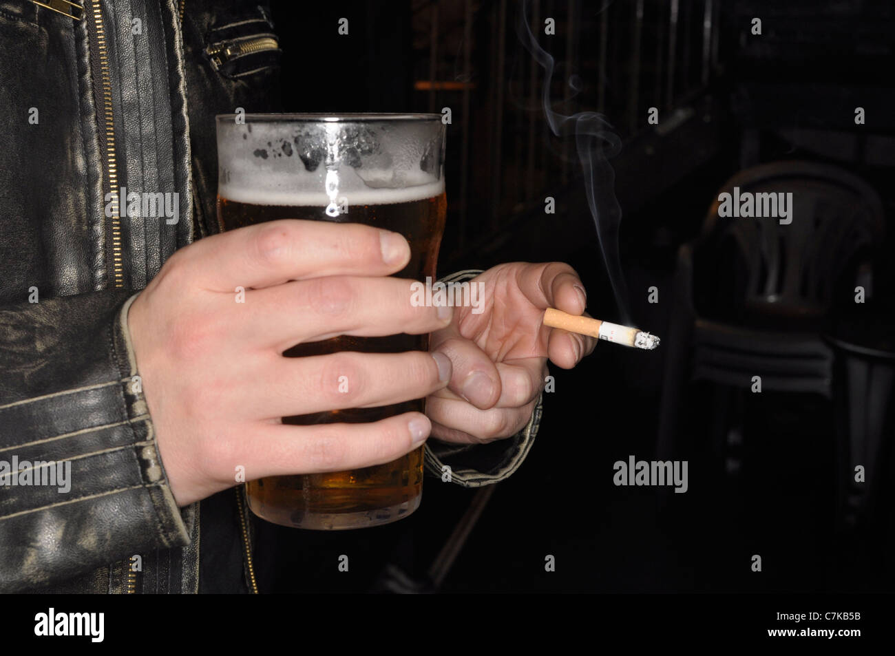 Holding as pint and smoking a cigarette - Stock Image