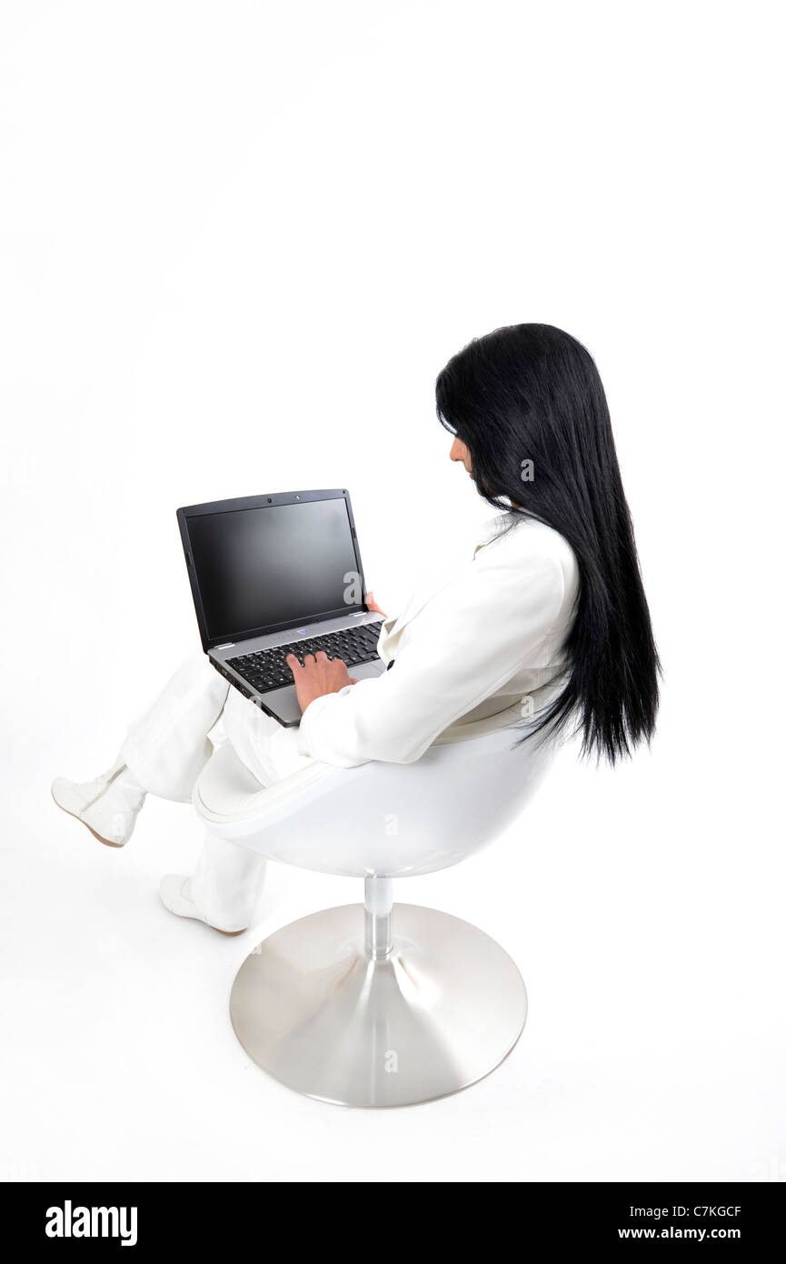 Young Indian businesswoman with laptop, mobile phone - Stock Image