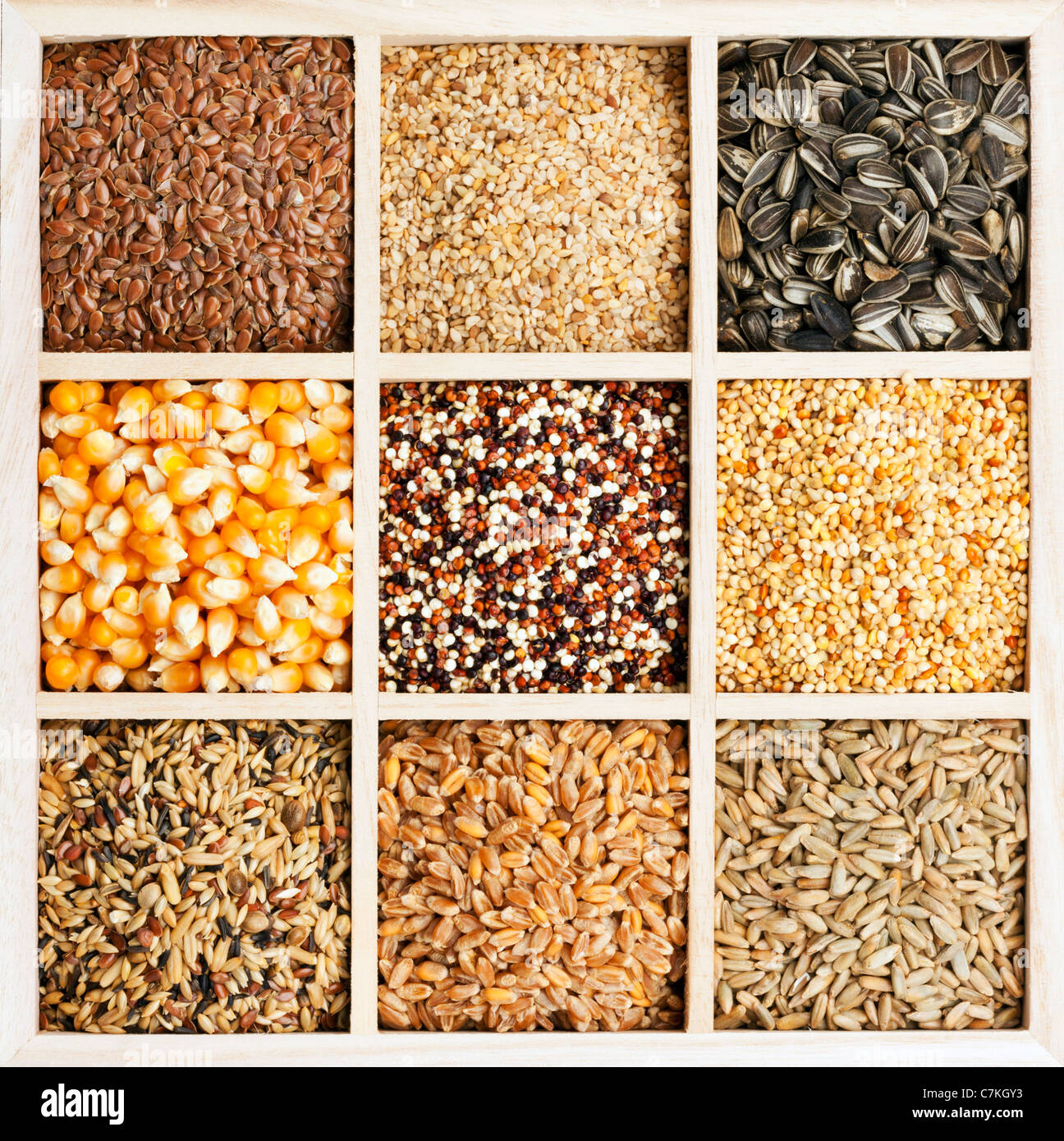 variety of seeds and grains in square wooden box - Stock Image