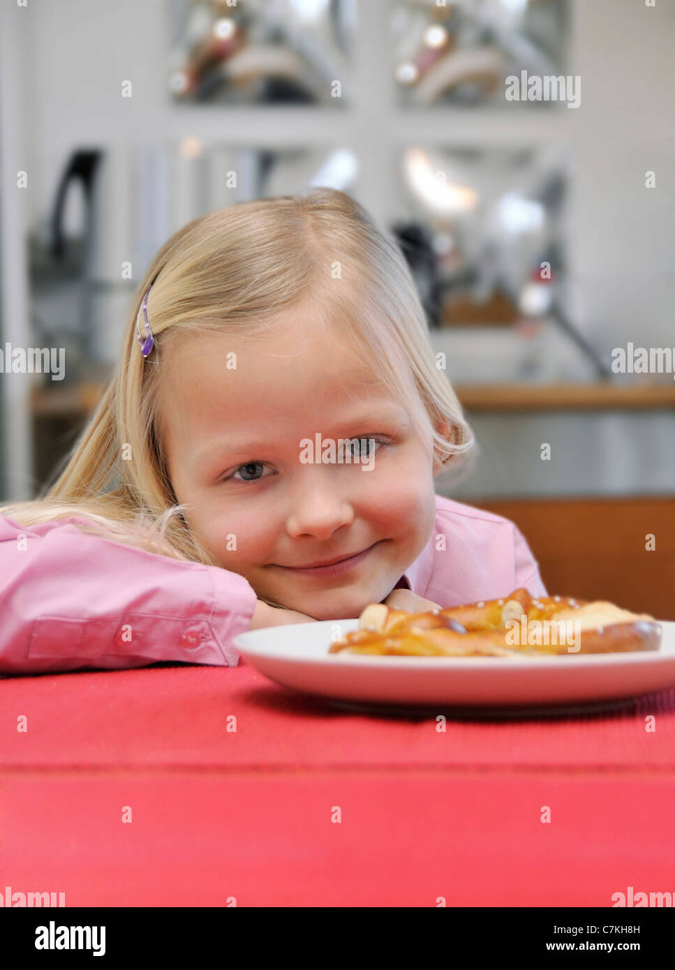 Young girl, 6, sitting at a table - Stock Image