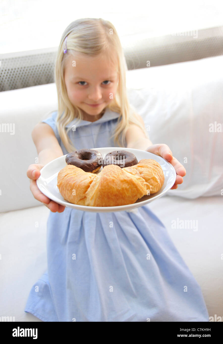Young girl, 6, with a blue dress presenting a plate with chocolate donuts and a croissant - Stock Image