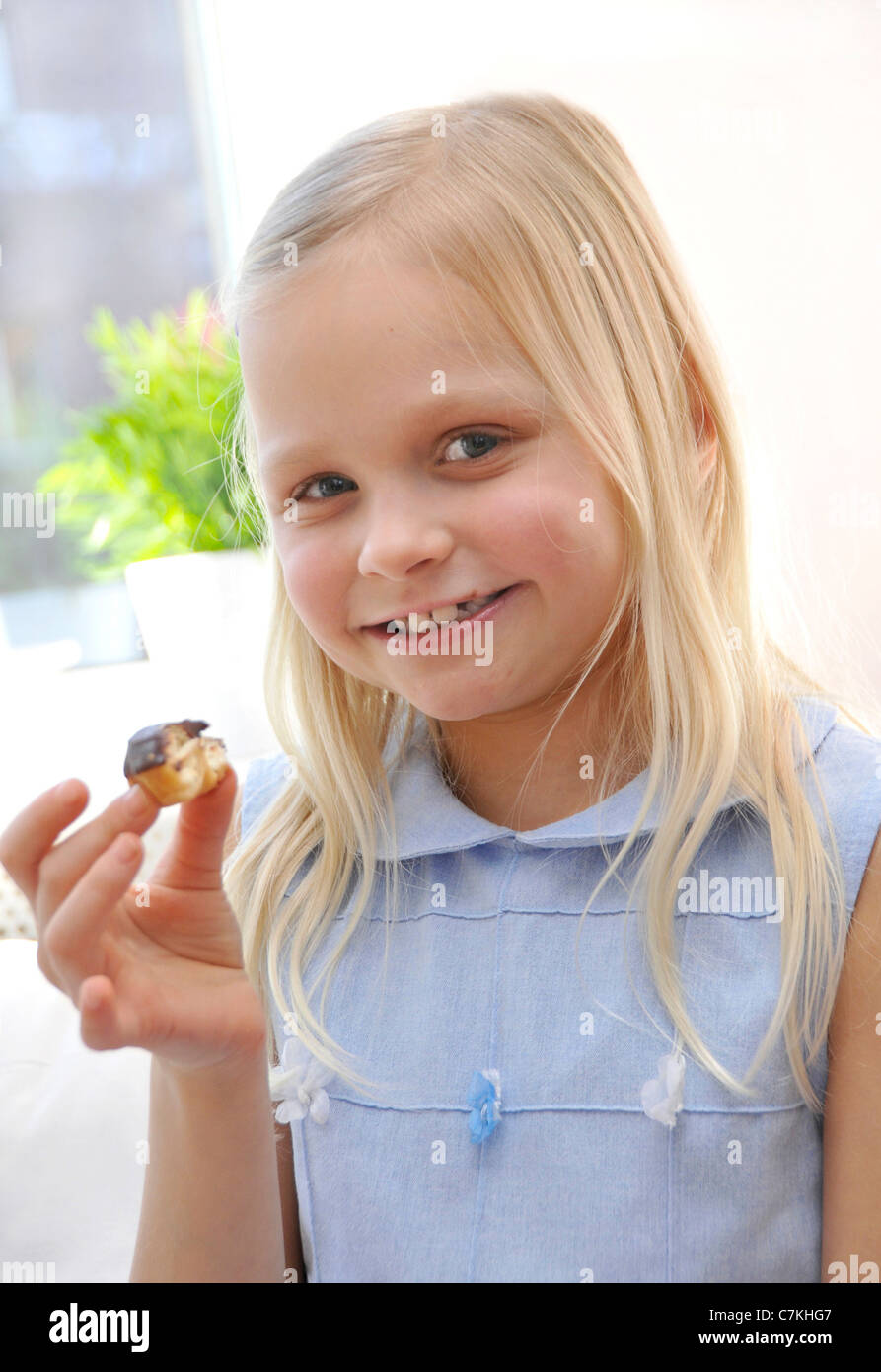 Young girl, 6, with a blue dress and a chocolate donut in her hand - Stock Image