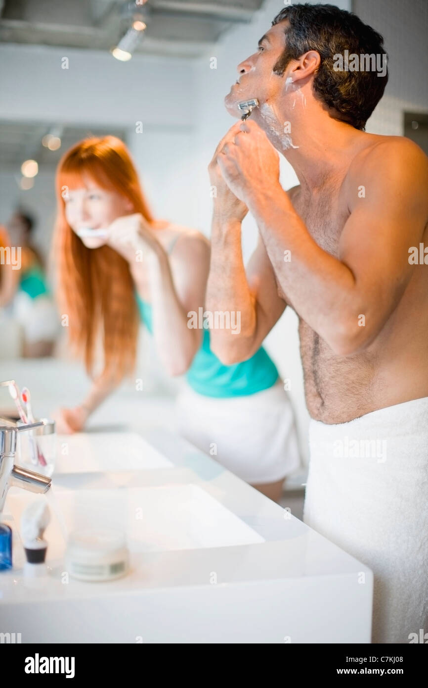 Couple brushing teeth and shaving - Stock Image