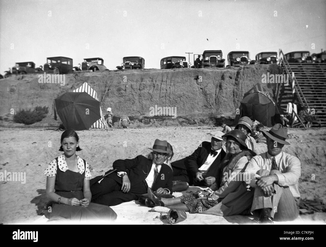 family and friends hanging out at southern california beach 1930s fashion group photo cars black and white Stock Photo