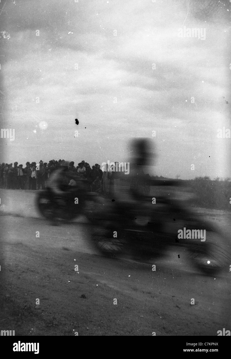1930s motorcycle race Americana blurred passing speed crowd watching racing fast - Stock Image