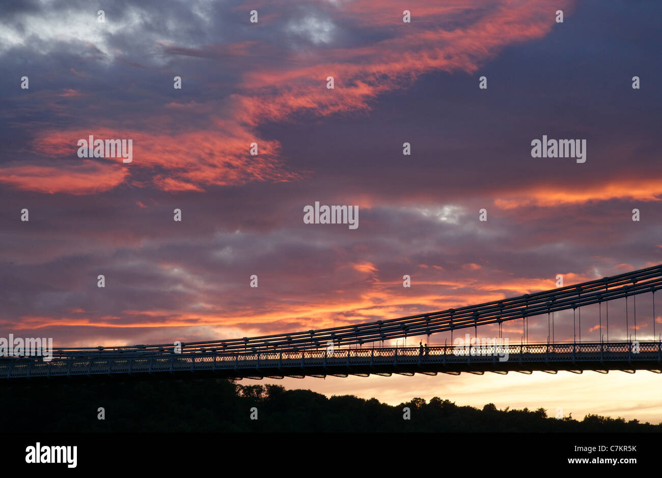 Two silhouetted figures walking over the Clifton Suspension Bridge in Bristol at sunset Stock Photo