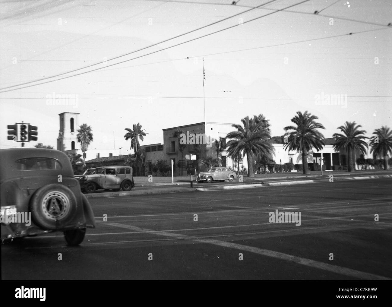 Los Angeles intersection with cars 1930s palm trees road travel buildings - Stock Image