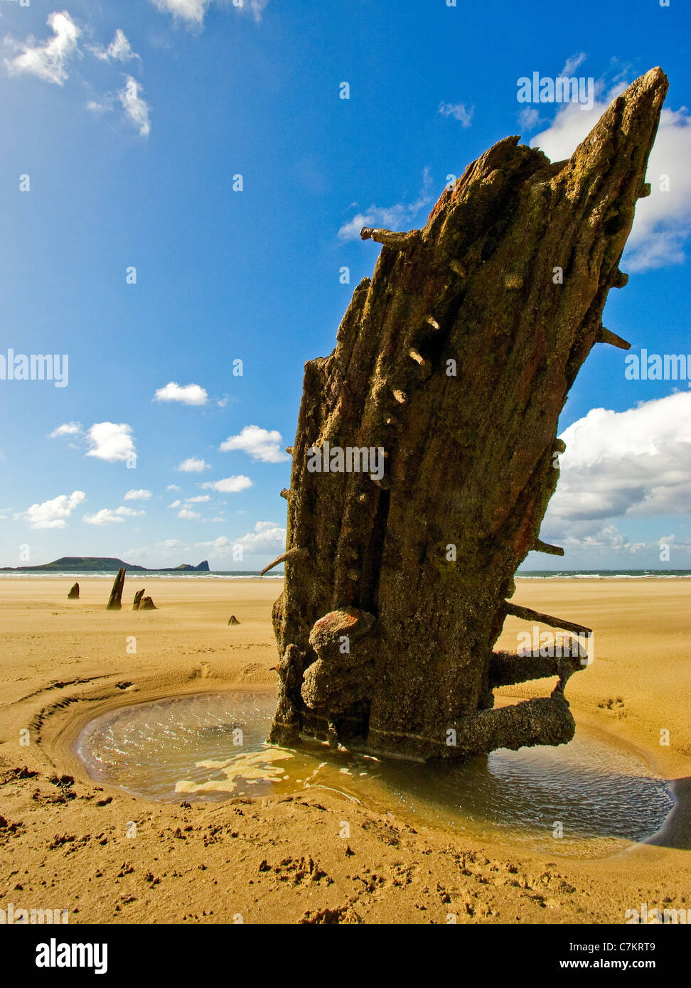 Vestigial remains of shipwrecked Helvetia protruding from the sands of Rhossili beach on the Gower peninsula in - Stock Image