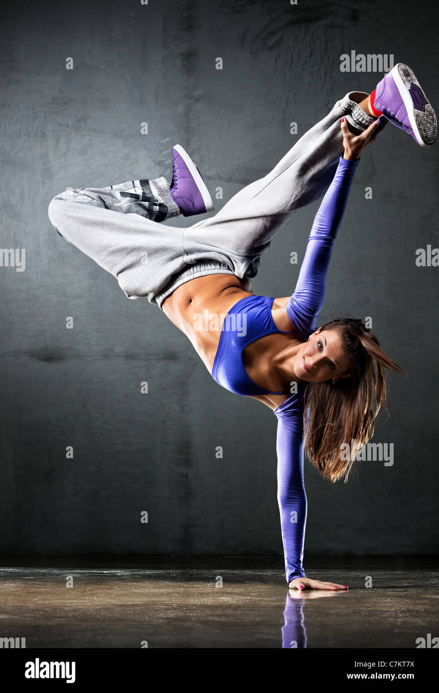 Young woman dancer on wall background. - Stock Image
