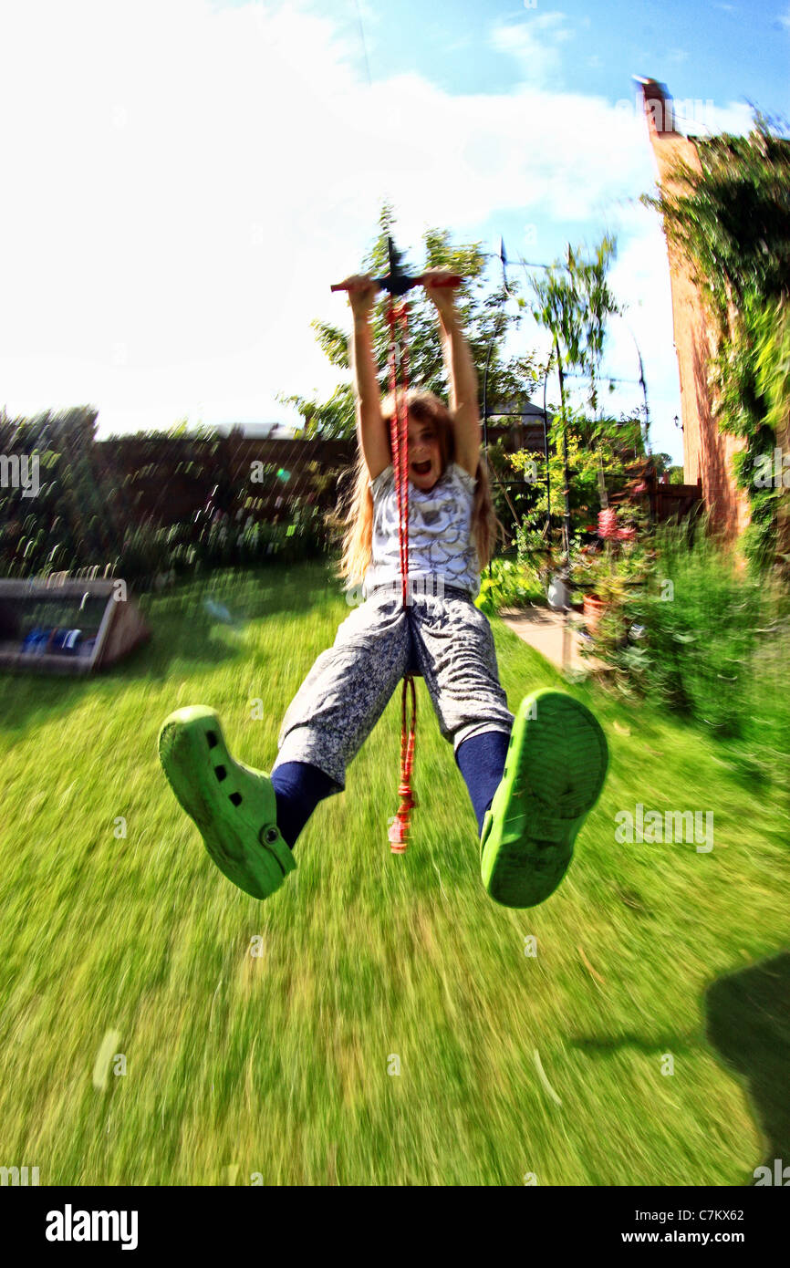 8 Year Old Girl On A Zip Wire In Garden   Stock Image