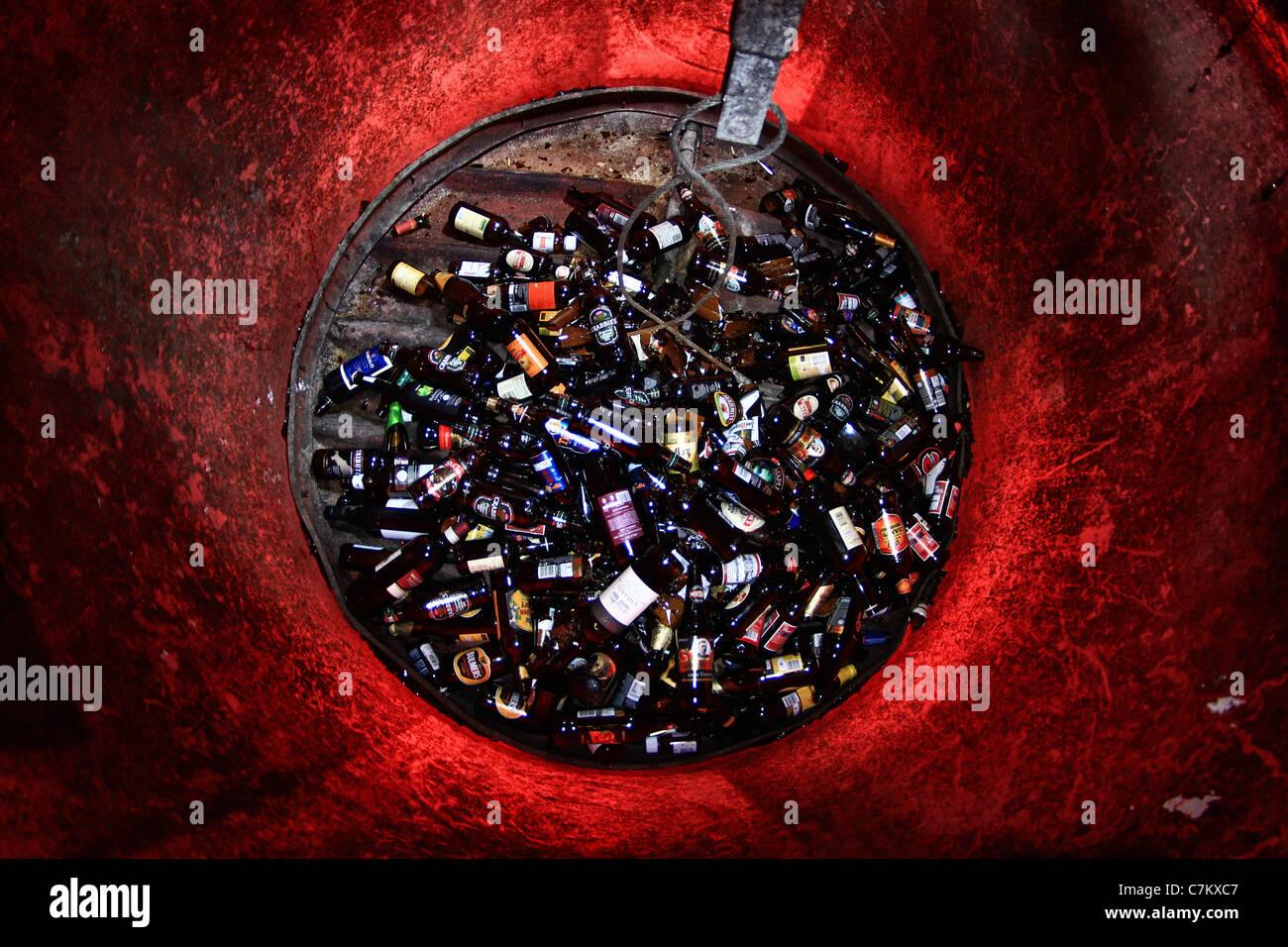 broken brown bottles in a bottle bank - Stock Image