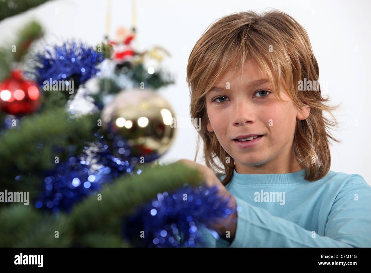 Prepubescent boy decorating a Christmas tree - Stock Image
