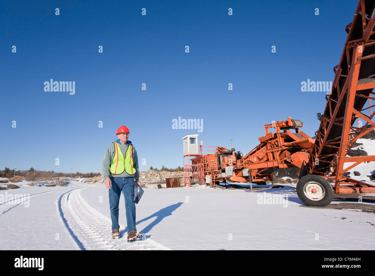 Engineer inspecting rock crusher at a construction site - Stock Image