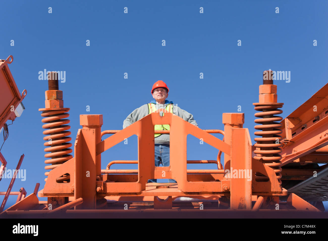 Engineer on a platform of rock crusher at a construction site - Stock Image