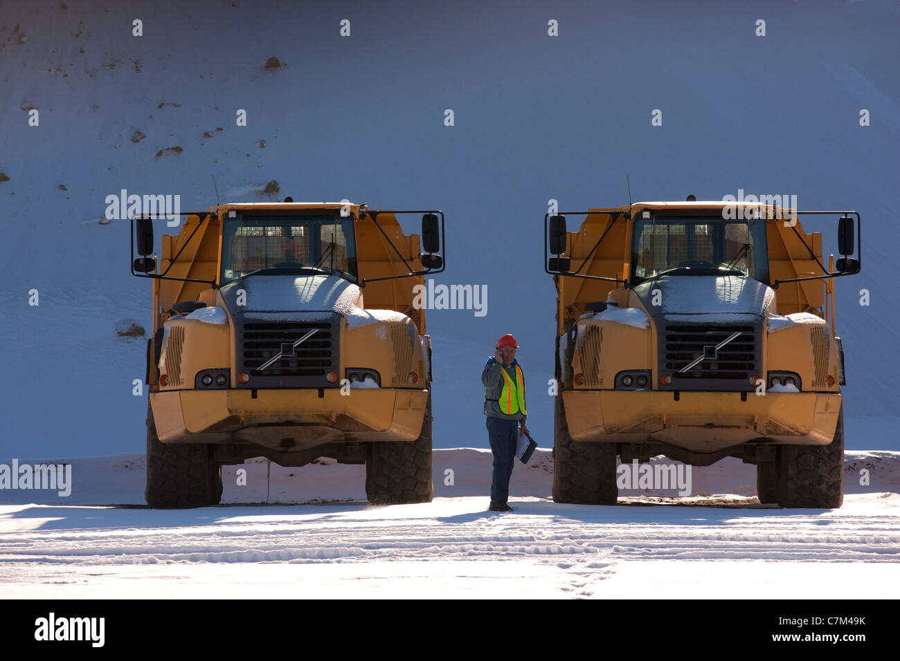 Engineer with earth movers at a construction site - Stock Image