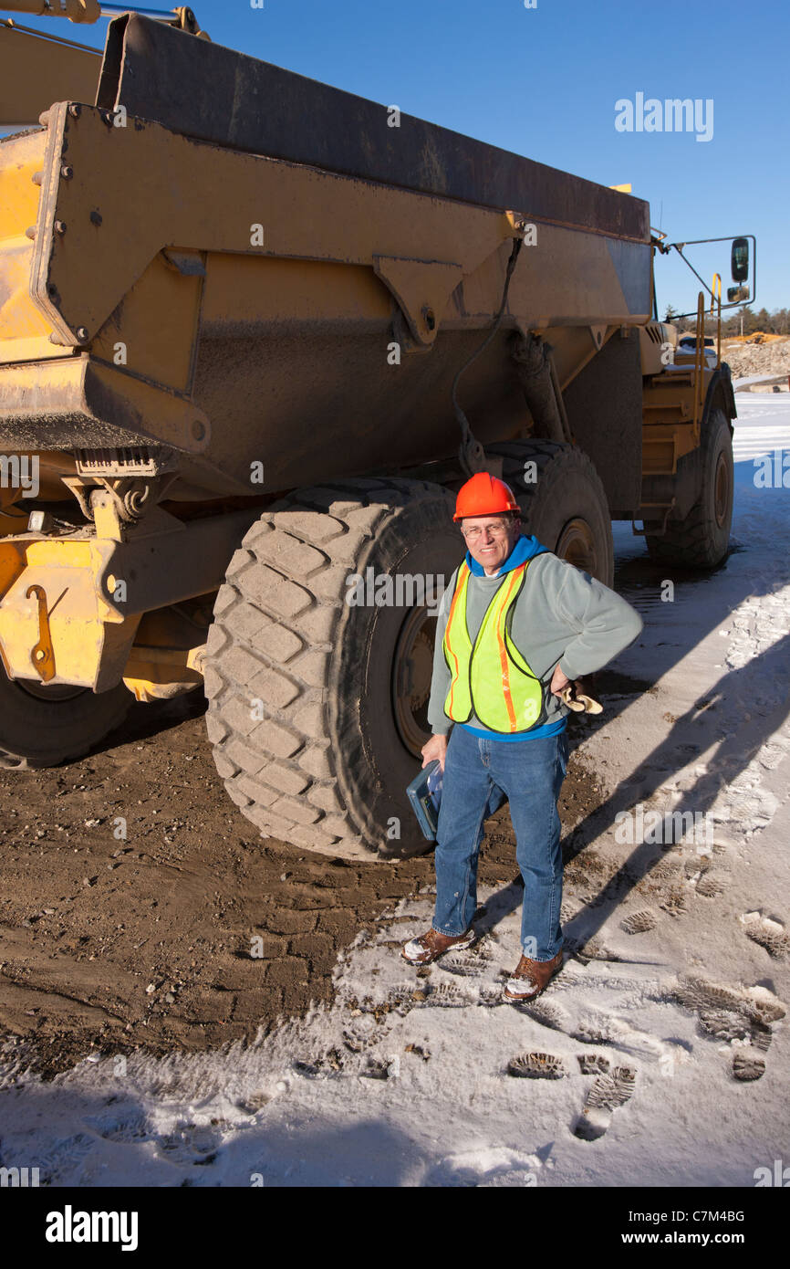 Engineer during inspection of earth movers at a construction site - Stock Image