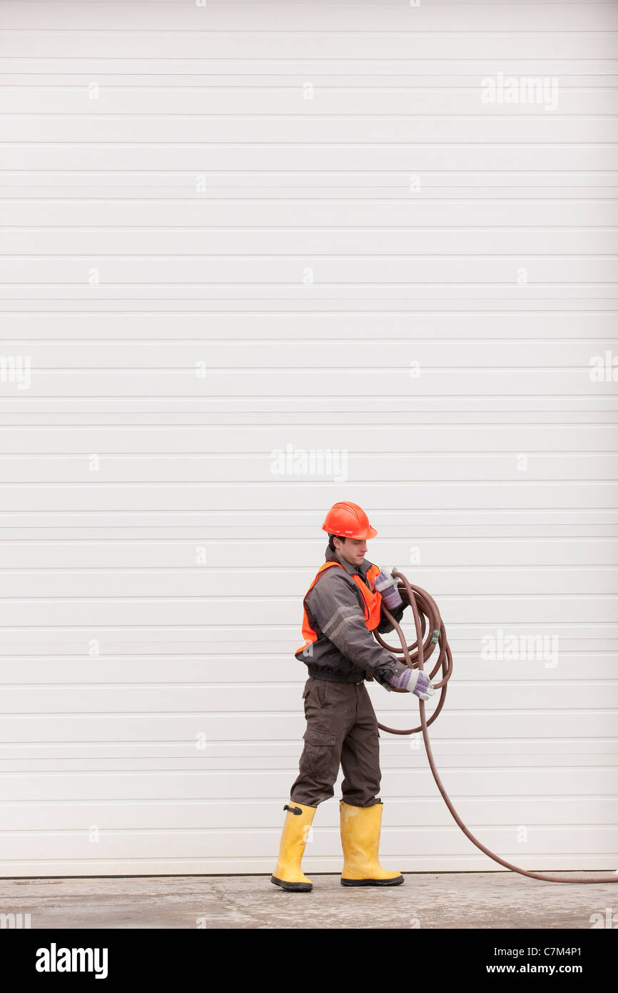 Transportation engineer coiling hose at industrial garage - Stock Image