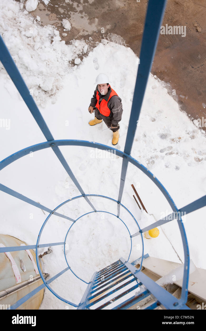 Engineer looking at safety enclosure for climbing an industrial tower - Stock Image