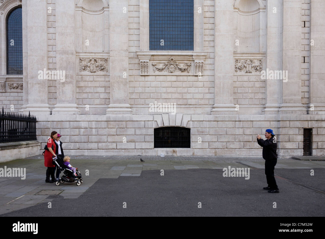 A tourist family pose for photos near London's St Paul's Cathedral. - Stock Image