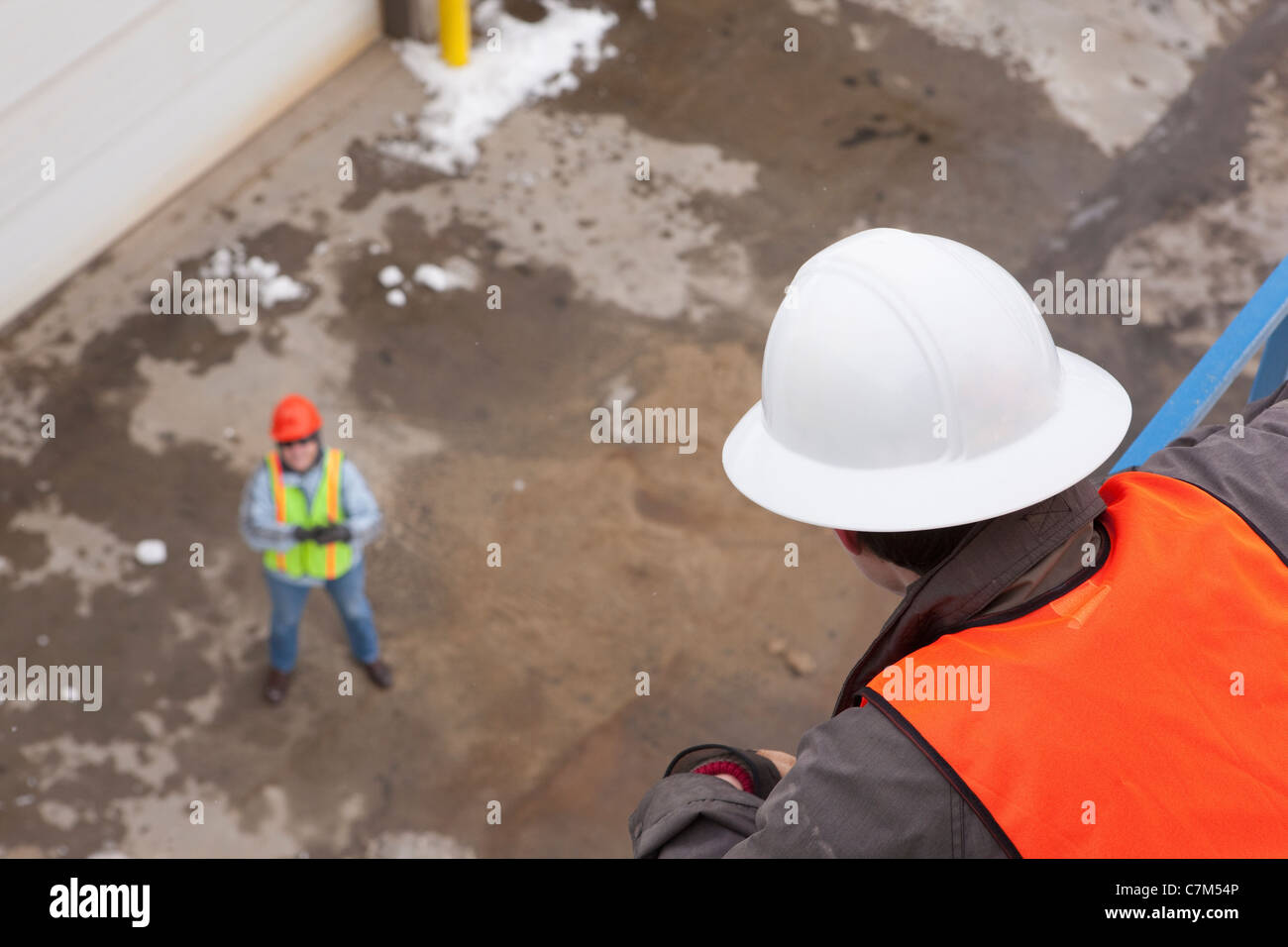Engineer talking to managing engineer from an industrial tower - Stock Image