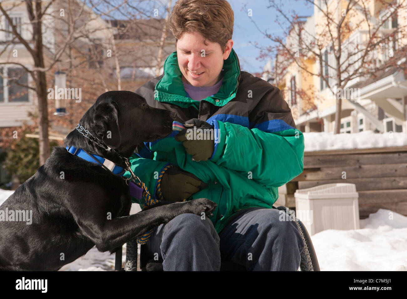 Woman with multiple sclerosis giving keys to a service dog - Stock Image