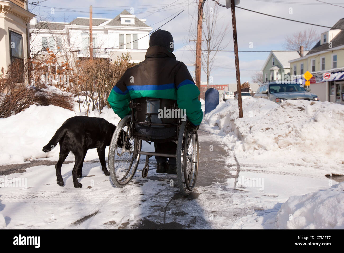 Woman with multiple sclerosis trying to get to the mailbox with a service dog - Stock Image