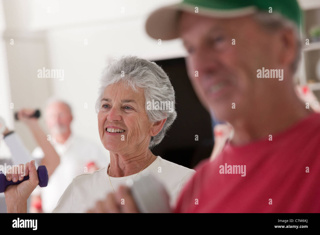 Seniors exercising with dumbbells in a health club - Stock Image