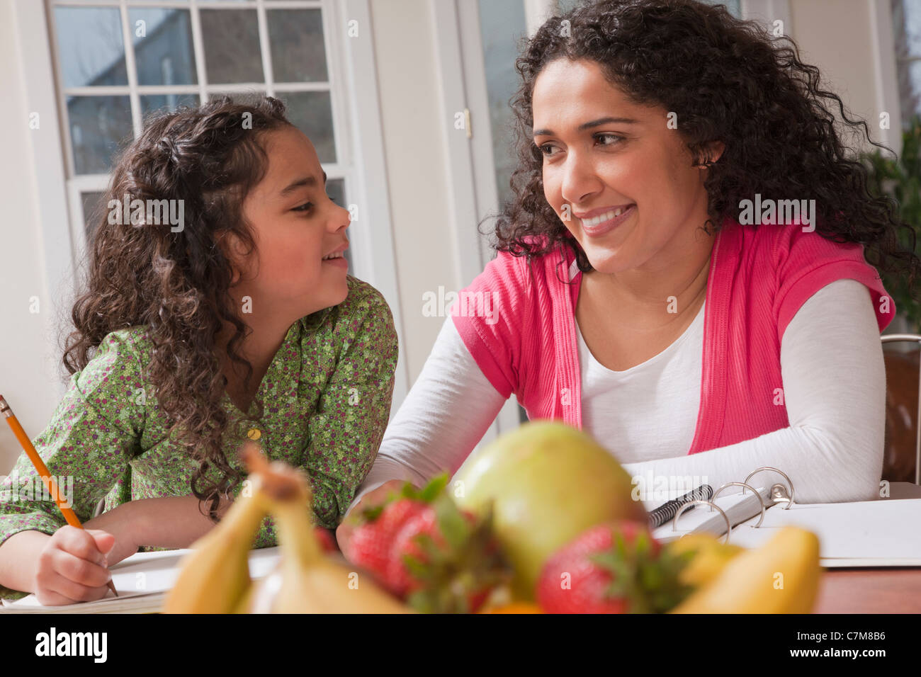 Hispanic woman assisting her daughter for study work - Stock Image