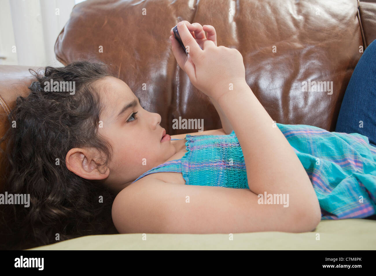 Hispanic girl lying on a couch and looking at a text message on a mobile phone - Stock Image
