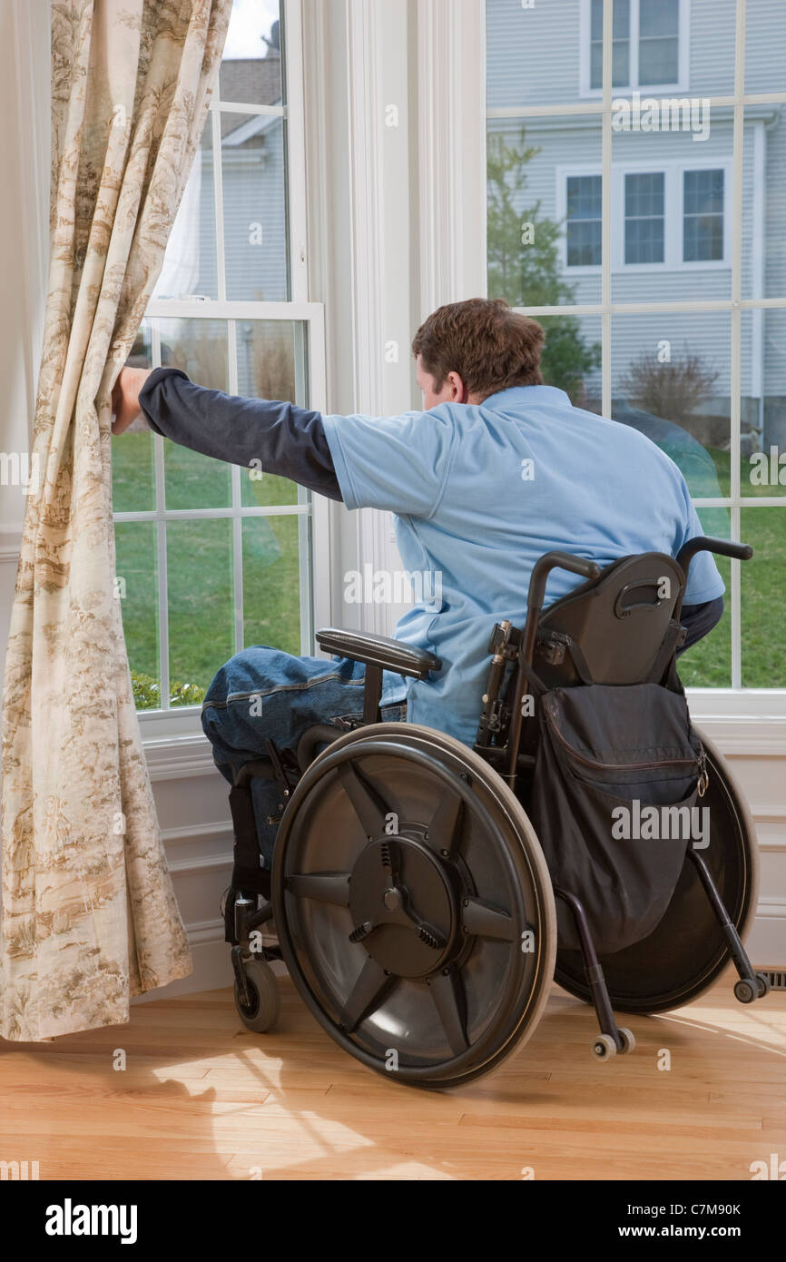Man with spinal cord injury in a wheelchair looking out the window of his accessible home - Stock Image