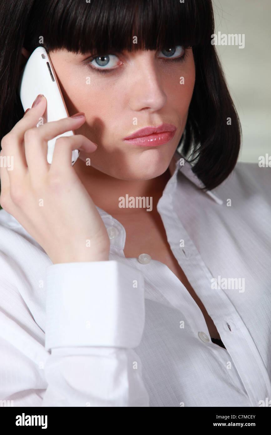 Upset brunette making telephone call - Stock Image