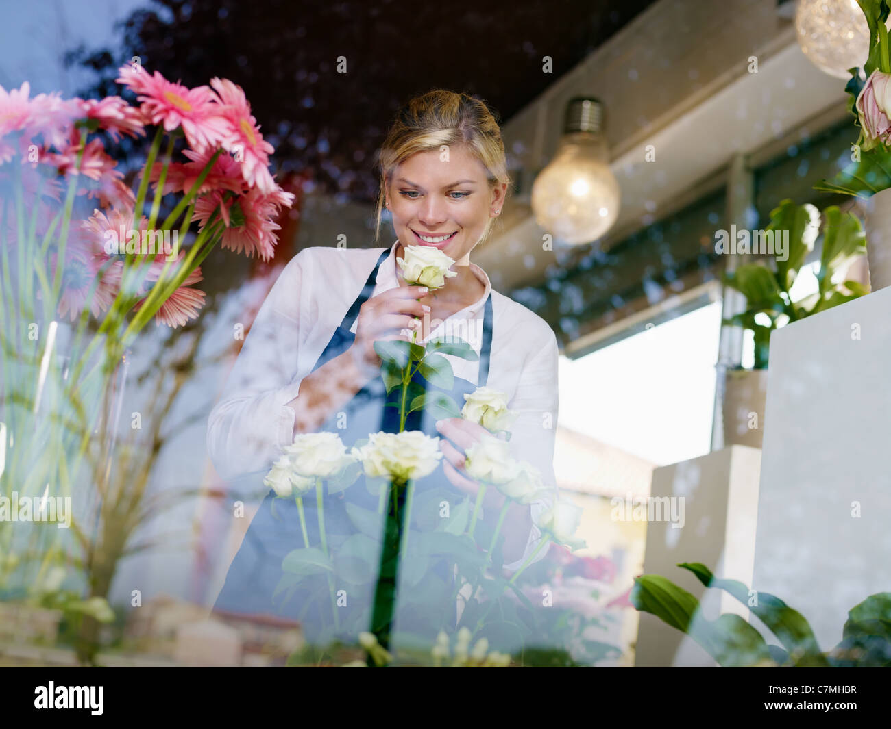 Young attractive woman working in flower shop, preparing bouquet and smelling white roses Stock Photo