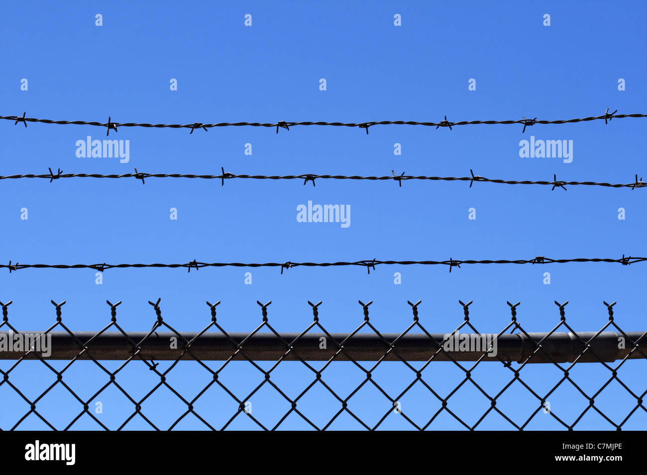 chain link and barb wire fence top with blue sky background and copy space - Stock Image