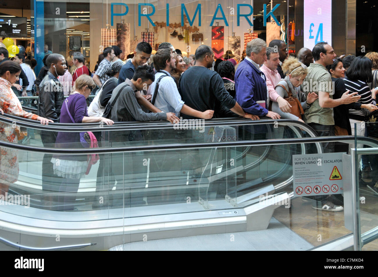 Group of people shoppers on busy indoor down escalator Westfield shopping centre mall outside Primark clothing store - Stock Image