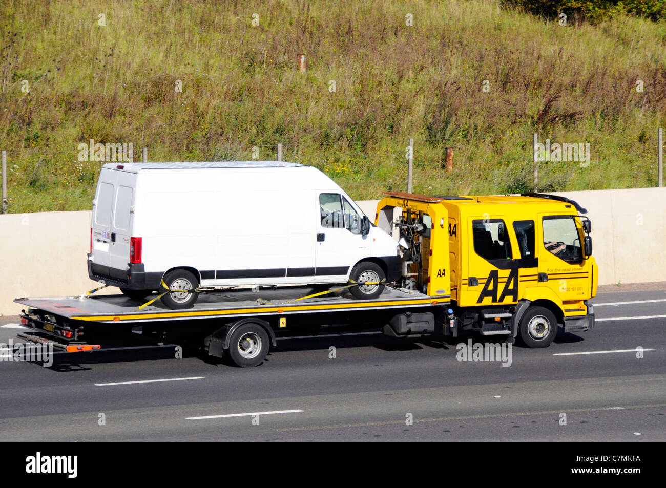 Side view of AA rescue breakdown recovery lorry truck transporter transporting unmarked white van driving along - Stock Image