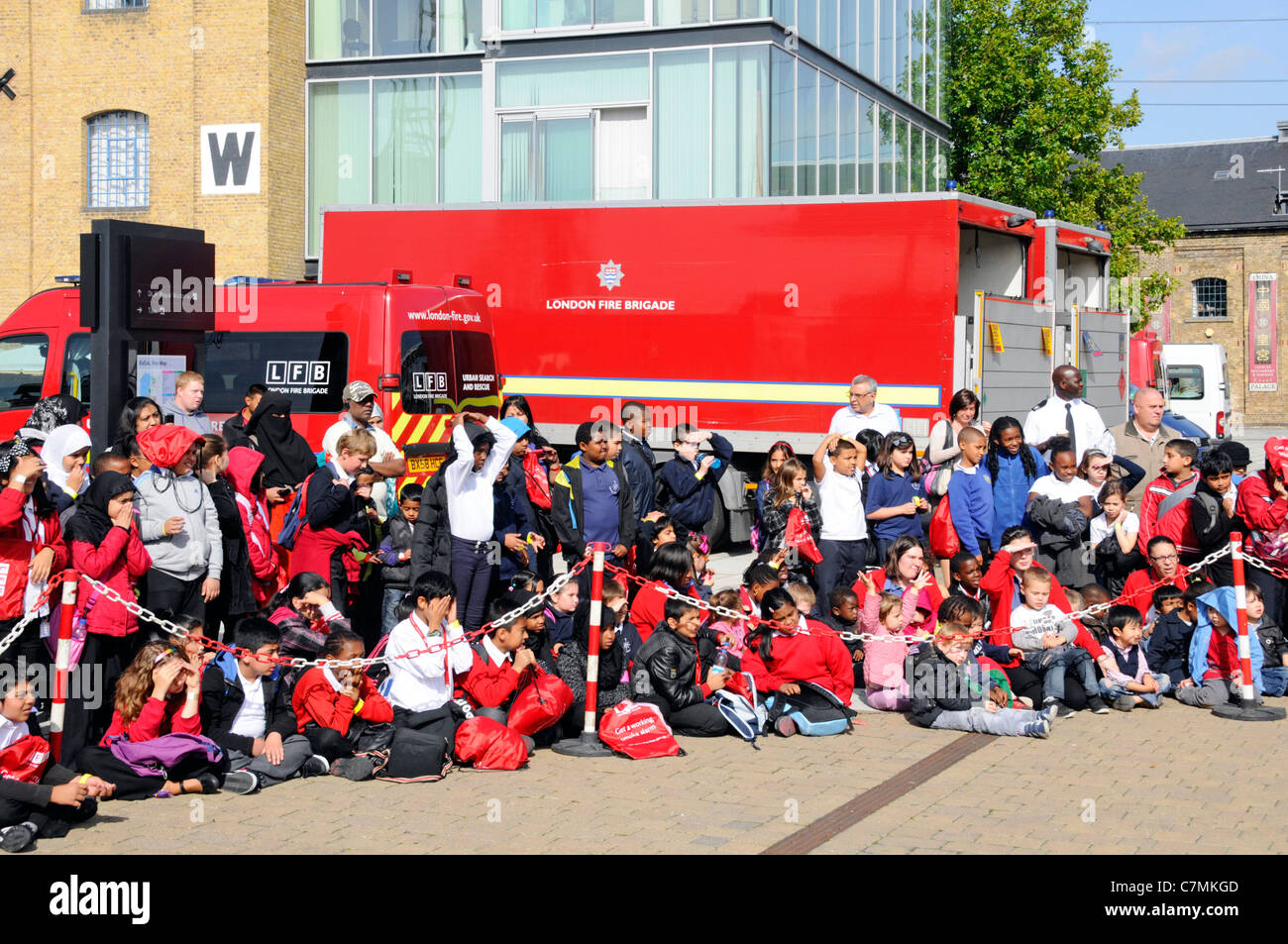 School children awaiting a fire safety talk and demonstration by London Fire Brigade The Excel Centre London England - Stock Image