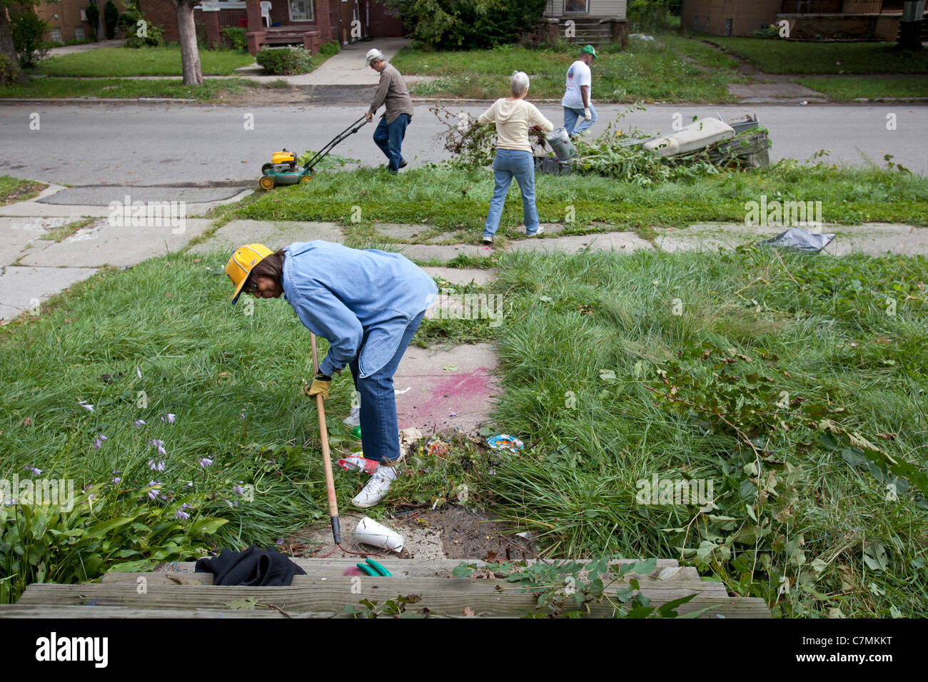 Detroit, Michigan - Members of the Three Mile Drive block club clean trash and weeds from a vacant home in their - Stock Image