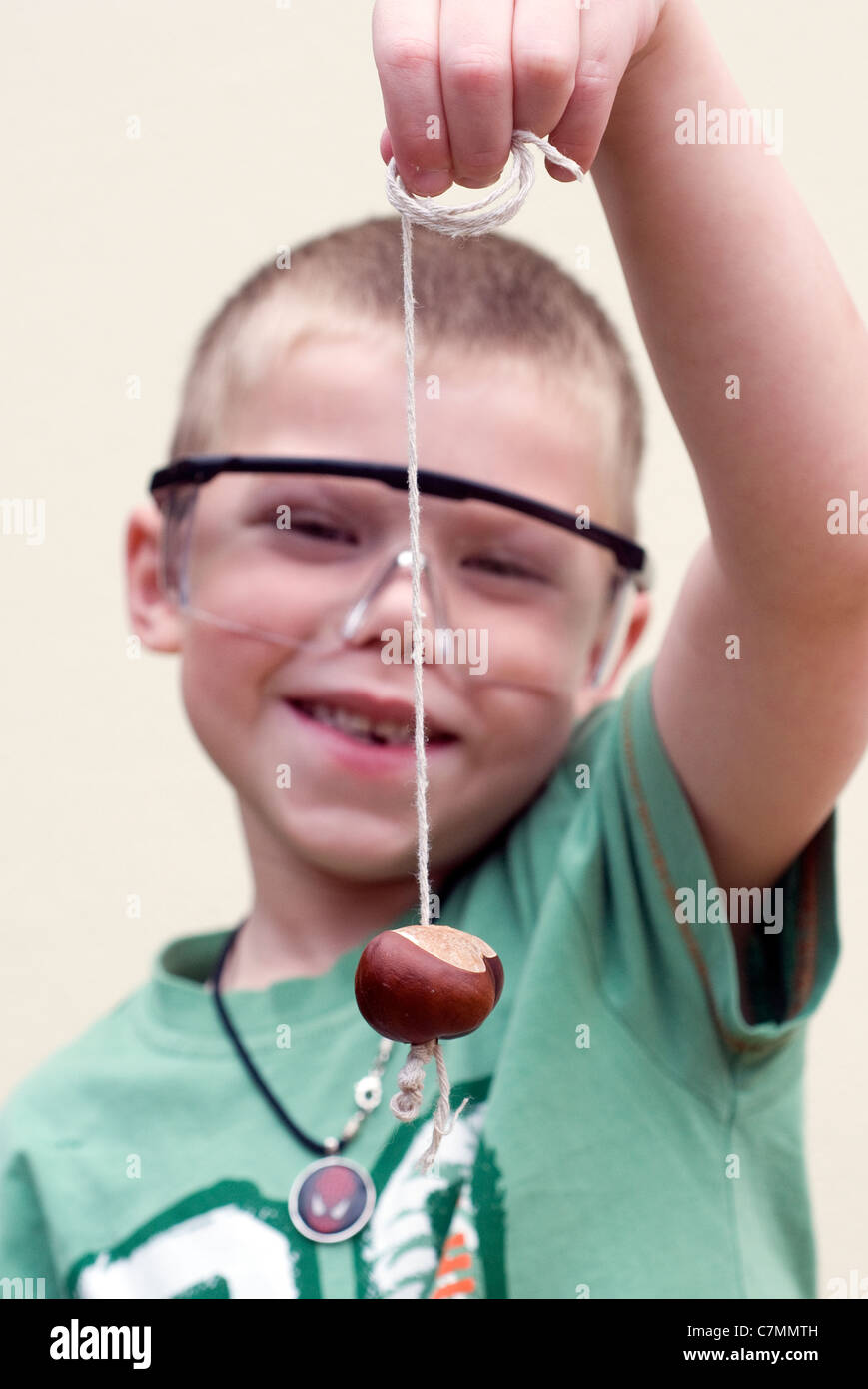 Boy playing Conkers with Safety glasses on, chestnut, conkers, cutout, game, hand, holding, horse, horse-chestnut, - Stock Image
