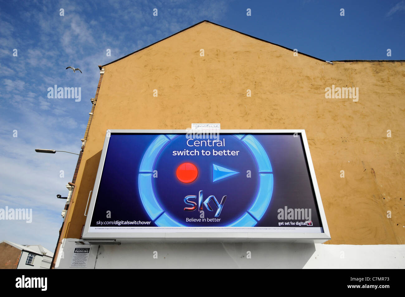 Sky broadband advertisement board featuring a 'play' and 'record symbol' on the side of a shop with - Stock Image