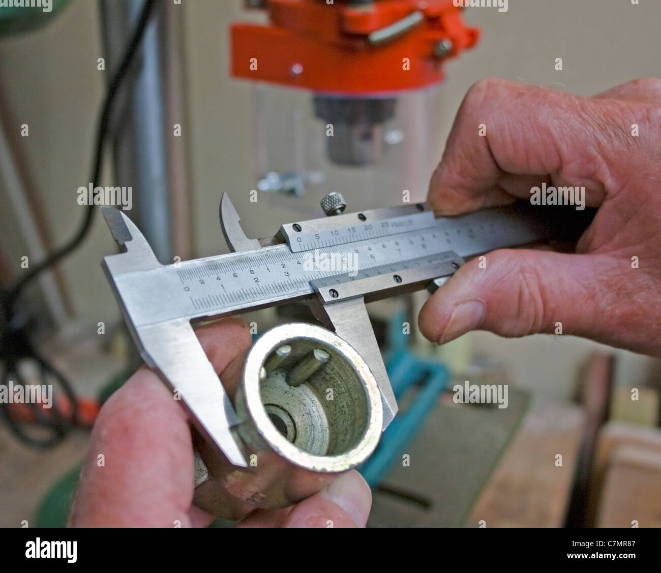 Measuring a socket with vernier callipers close up of hands - Stock Image