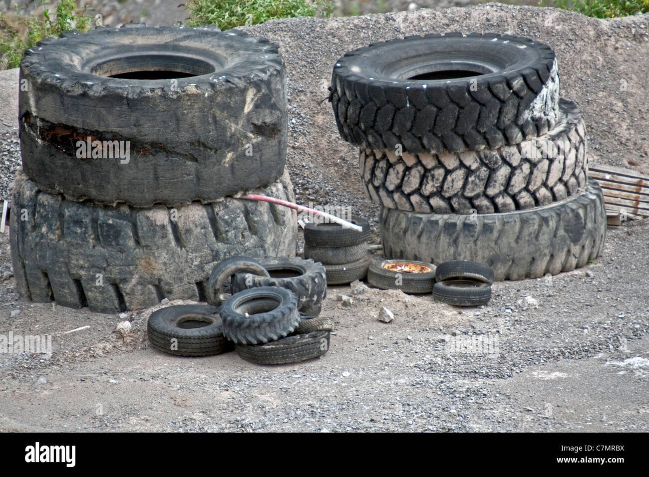 Dumped worn out tyres from various vehicles in a quarry - Stock Image