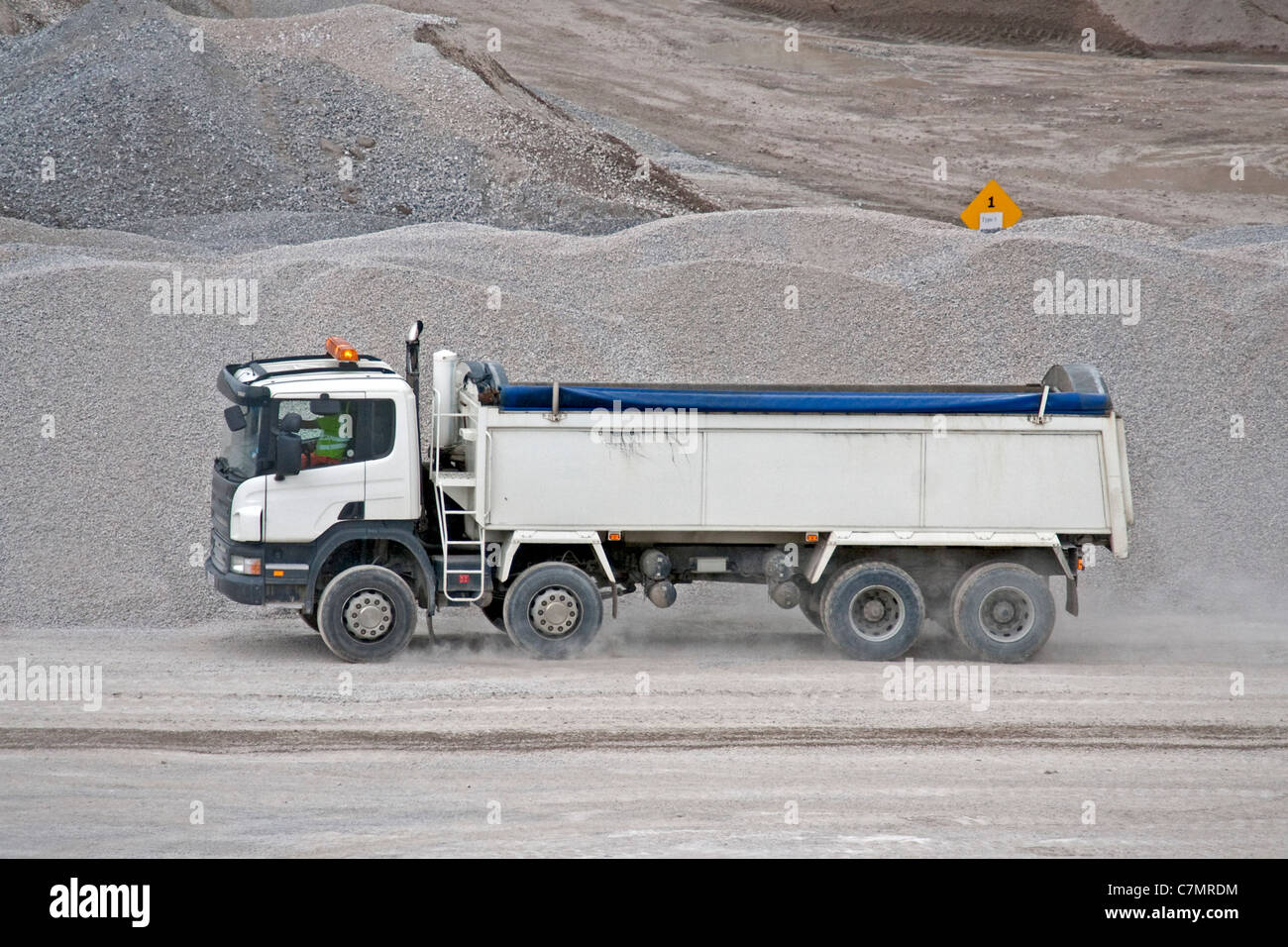A white 8 wheel tipper truck going for a load of stone in a quarry - Stock Image