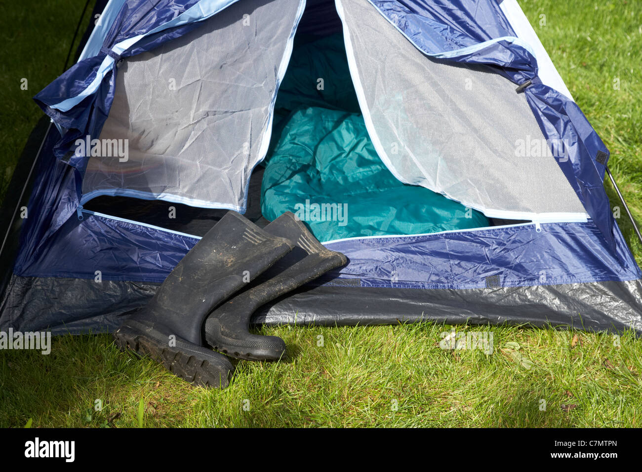 dirty wellington boots lying in front of an open tent door Stock Photo