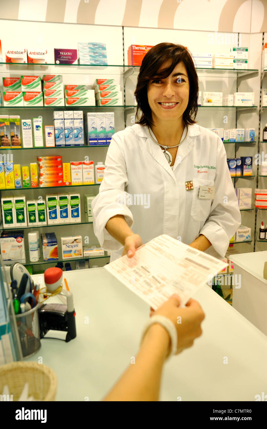 Pharmacist standing in pharmacy (give prescription) - Stock Image