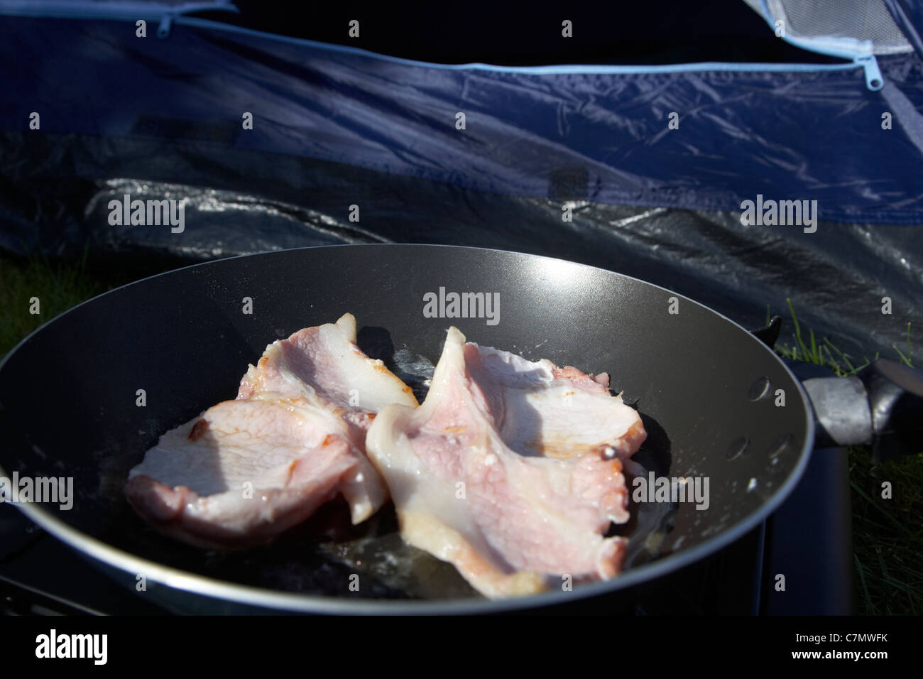 frying bacon on a small portable gas cooker in front of an open tent door - Stock Image