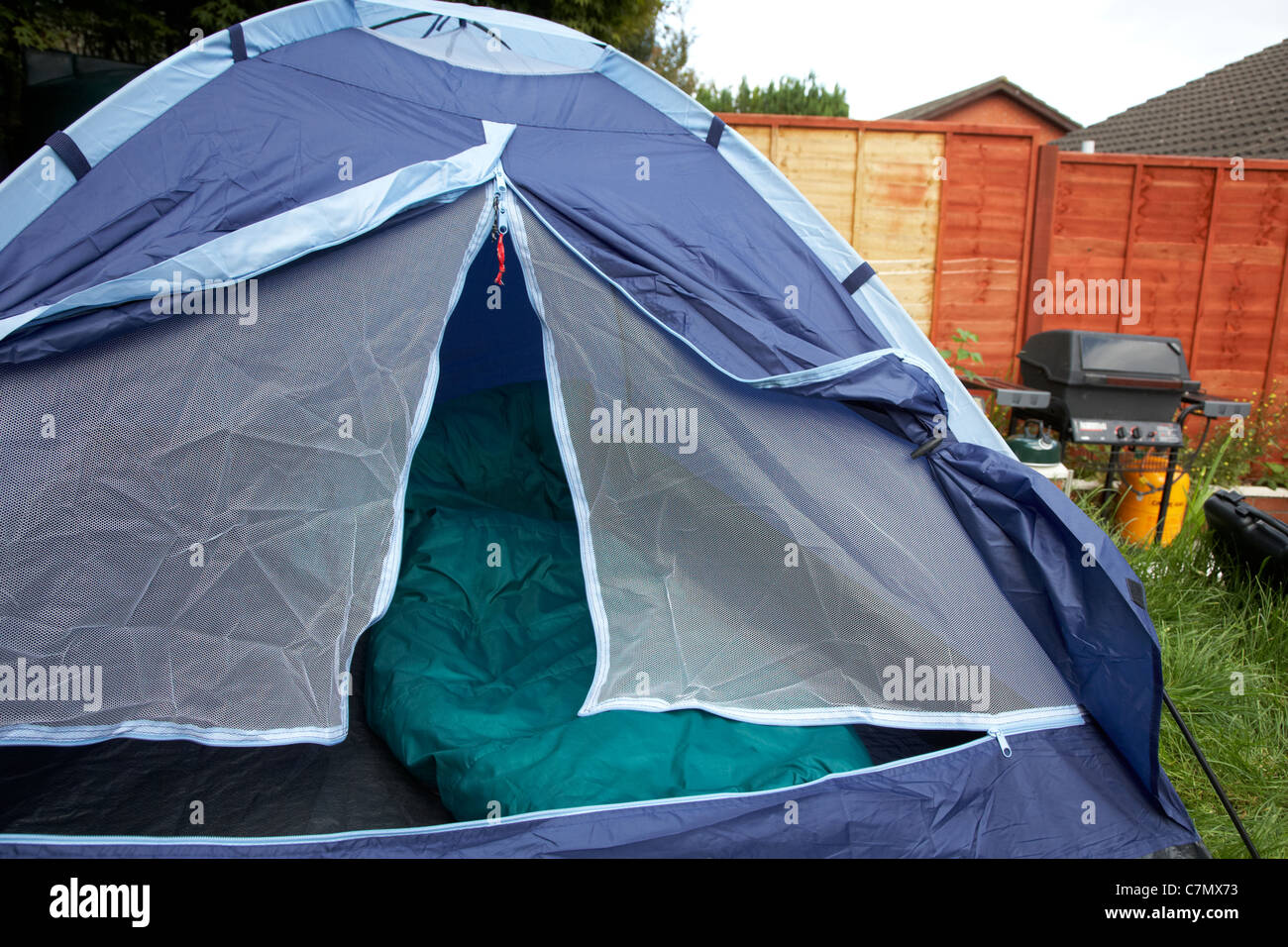 front door left open on a small dome tent pitched in the garden of the house in the uk - Stock Image